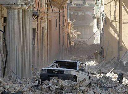 Un coche atrapado entre los cascotes de los edificios derrumbados por el seísmo en la localidad de L'Aquila, capital de los Abruzos.