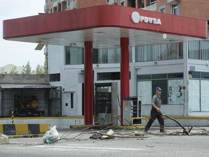 Un hombre camina frente a una gasolinera de PDVSA, en San Cristóbal (Venezuela).