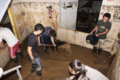 Un grupo de jóvenes lleva a cabo labores de limpieza en el auditorio de Guadamur (Toledo), este jueves.