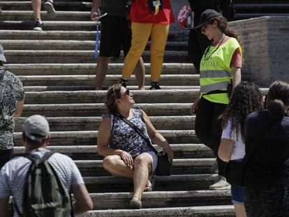 Una policía pide a una mujer sentada en la escalinata de la Plaza de España en Roma que se levante.
