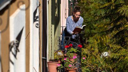 Una chica lee un libro en el balcón de su casa, durante el confinamiento en Barcelona.