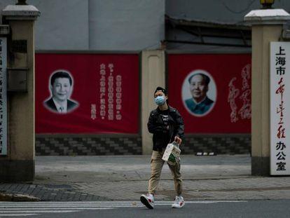 Un hombre con una máscara camina frente a los retratos del presidente chino Xi Jinping y el difunto presidente Mao Zedong, el pasado 10 de febrero en Shanghái.