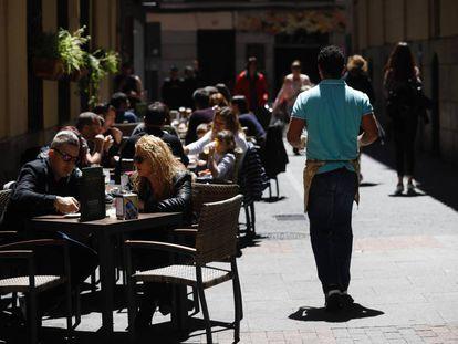 Un camarero sirve en una terraza en Madrid