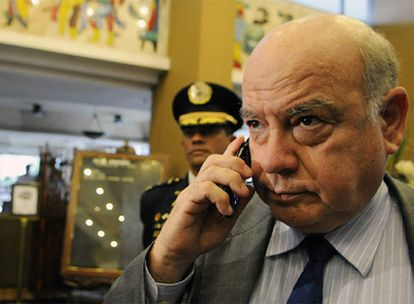 El secretario general de la OEA habla por teléfono escoltado por agentes a su llegada a Tegucigalpa.