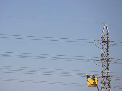 Varios operarios trabajan en un tendido eléctrico a las afueras de Sevilla, el pasado 1 de julio.