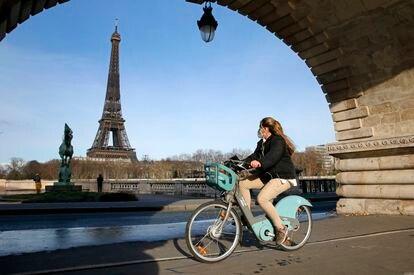 Una mujer se mueve con una bicicleta pública de París.