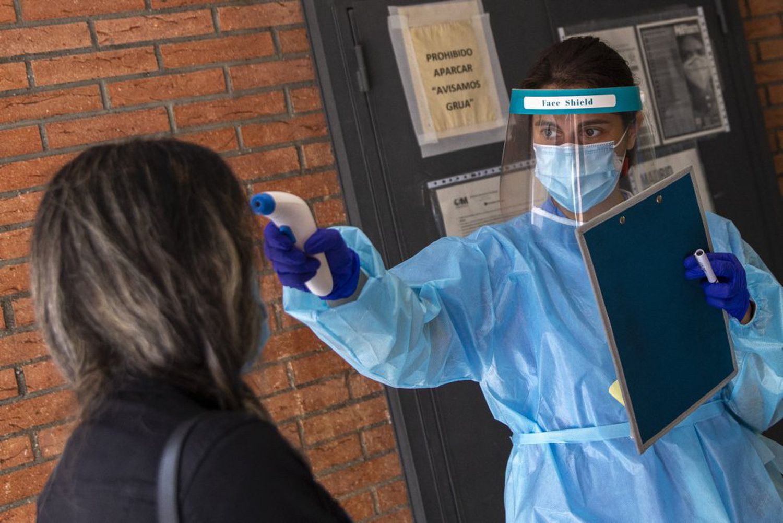 Una enfermera mide la temperatura a una mujer en la entrada del centro de salud de Puerta Bonita, en Madrid, este miércoles.