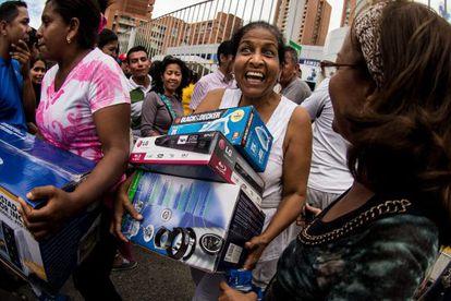 Decenas de personas sacan electrodomésticos de una tienda.