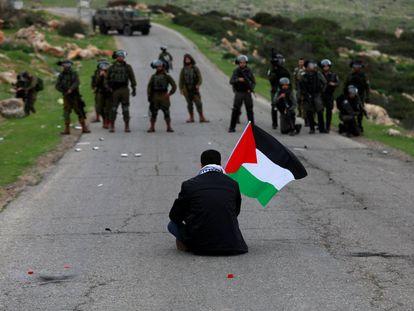 Un manifestante con una bandera palestina se sienta frente a las fuerzas israelíes durante una protesta contra los asentamientos israelíes en febrero.