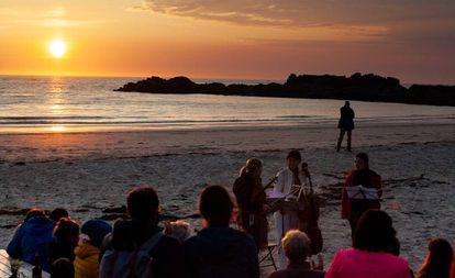 Tres miembros del Cuarteto Sonoro tocan en la medianoche del martes en la playa de Gimsøy.