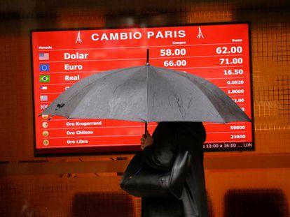 Una mujer que se protege de la lluvia pasa por delante de la pizarra de una casa de cambio de divisas.