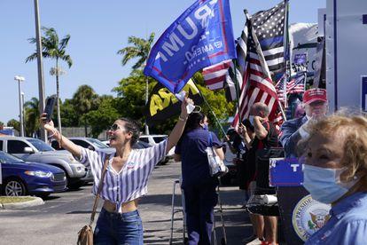 Una joven se toma una foto delante de un centro de votación donde hay seguidores de Trump en Hiealeah, Florida.