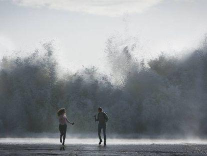 Una pareja corre tras hacerse un selfie mientras pican las olas en el espigón del Bogatell de Barcelona el pasado 23 de enero.