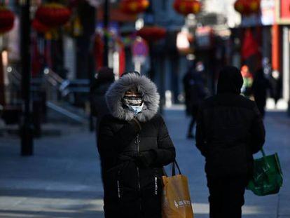 Una mujer pasea por Pekín con una máscarilla para prevenir el contagio del coronavirus.