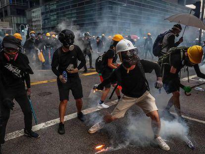 Manifestantes responden a los gases lacrimógenos lanzados por la policía este sábado en Hong Kong. En vídeo, imágenes de los enfrentamientos.