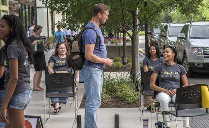 Voluntarias de Sidewalk Talk, sentadas, se ofrecen a charlar en Fairfax.
