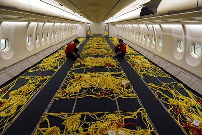 Empleados de Iberia adaptan el interior de un avión de pasajeros  para convertirlo en uno de carga en el aeropuerto de Madrid-Barajas durante la pandemia.