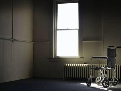 En la imagen, una silla de ruedas en una habitación vacía.
