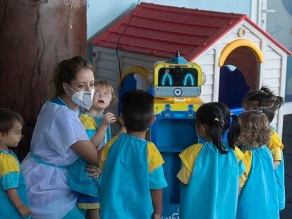 Una educadora muestra a los niños un robot que toma la temperatura en una escuela infantil, esta mañana en Madrid