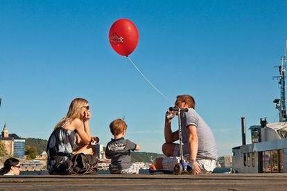 Una familia en el puerto de Oslo, frente al Centro Nobel de la Paz.