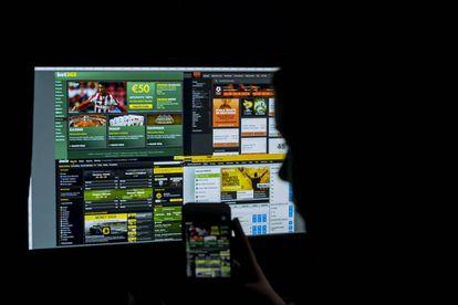 Un joven mira una pantalla de un ordenador con varias páginas web de apuestas online.
