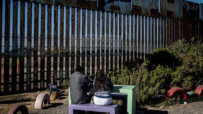 Una pareja de mexicanos pasa la tarde frente al muro fronterizo de Tijuana.