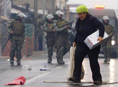 Una mujer acarrea mercancías robadas en Concepción.