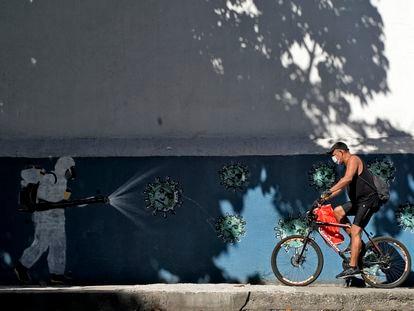 Un hombre en bicicleta pasa ante un mural sobre el coronavirus en Río de Janeiro el pasado 8 de julio.