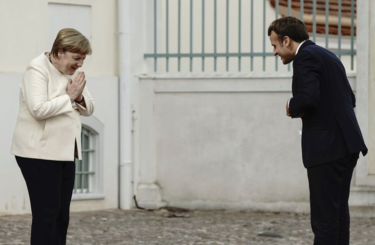 German Chancellor Angela Merkel and French President Emmanuel Macron greet each other from a distance at the gates of Meseberg Castle on Monday, north of Berlin.