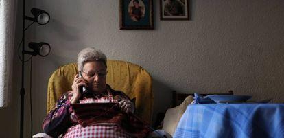 Una mujer teje mientras habla por teléfono en su casa.