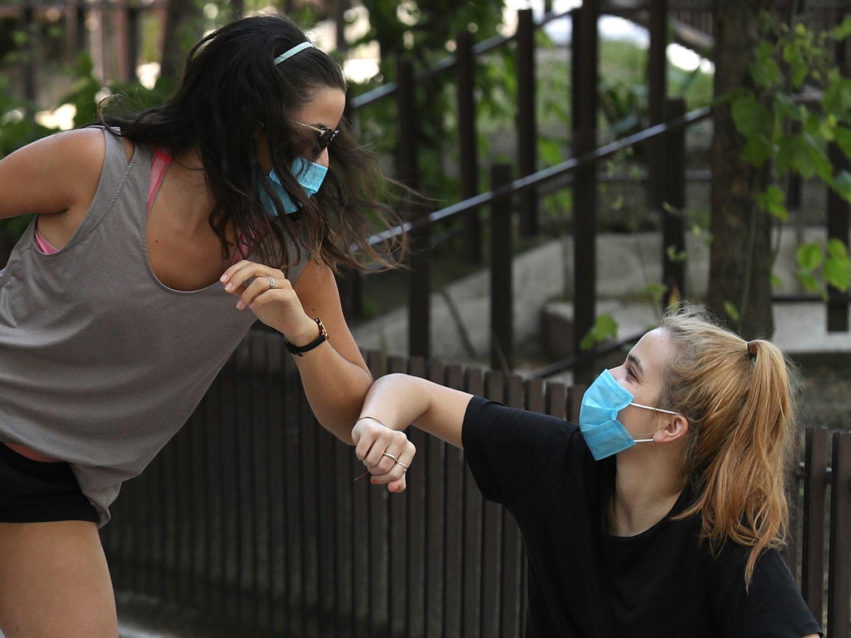 Dos chicas se saludan con los codos en Madrid.