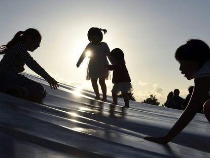 Varias niñas juegan en un tobogán en un parque.