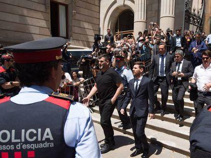 El jugador del FC Barcelona Lionel Messi (c) y su padre, Jorge Horacio Messi (detrás), sale de la Audiencia de Barcelona tras declarar en la tercera jornada del juicio.