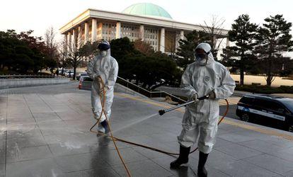 Personal sanitario desinfecta las calles en Seúl, Corea del Sur.