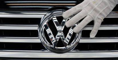 Una imagen de un empleado de Volkswagen tocando el logotipo de la marca