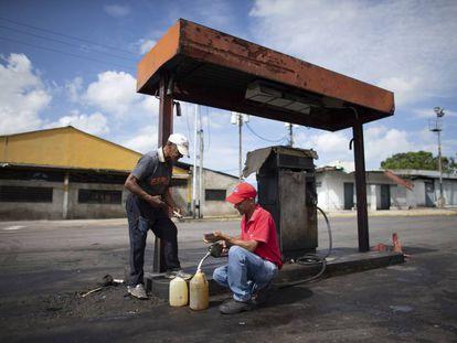 Dos hombres rellenan de gasolina unos bidones en Chivacoa (Venezuela), el 13 de octubre de 2019.