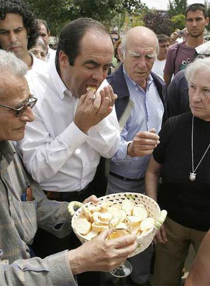 José Bono comulga ante la atenta mirada (detrás) de Pedro Zerolo