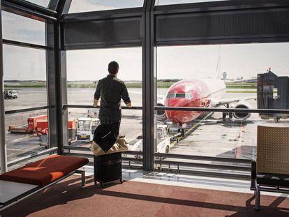 Un hombre observa un avión de Norwegian.