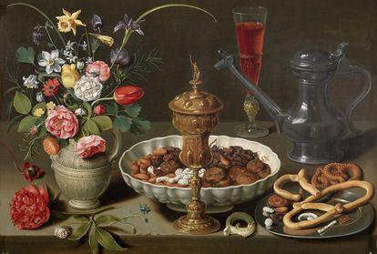 Bodegón con flores, copa de plata dorada, almendras, frutos secos, dulces, panecillos, vino y jarra de peltre.