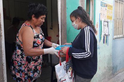 Una voluntaria del comedor comunitario la Fundación El pobre de Asís reparte la cena en la villa 31 de Buenos Aires. M.C