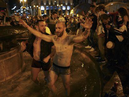 Dos jóvenes se bañan en una de las fuentes de la Puerta del Sol de Madrid en la madrugada del domingo, tras el fin del estado de alarma.