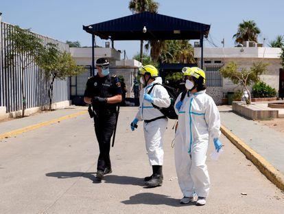 Dos sanitarios hablan con un policía en la puerta del Centro Temporal de Inmigrantes de Melilla.
