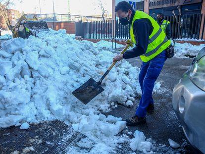 Un operario limpia nieve del alcantarillado de Madrid antes de que comiencen las lluvias.