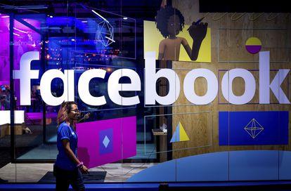 Una persona pasa frente a un cartel de Facebook durante F8, la conferencia anual de desarrolladores que celebra la compañía en San José, California.