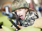 Niña juega en el salón de su casa a ser una soldado.