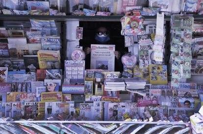Un quiosquero sostiene una copia de 'La Reppublica' en un puesto en Livorno, Italia.