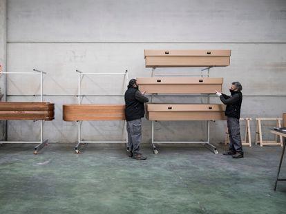 Trabajadores de la funeraria Eternam, la primera en España que pone en venta ataúdes de cartón,  colocan féretros