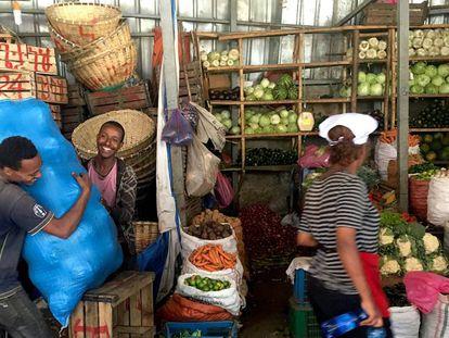 Una mujer con gorro blanco y delantal en el mercado de vegetales de Addis Abeba.