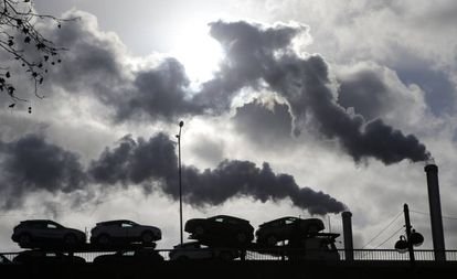 Un camión con coches atraviesa un puente de París ante el humo de una fábrica