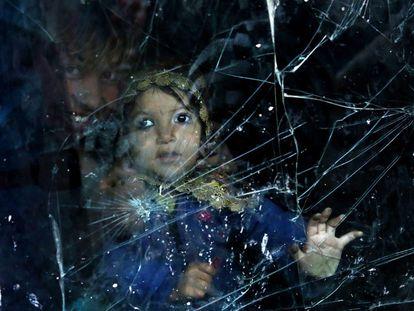 Una niña afgana desplazada mira a través de la ventana de su casa hecha de la luna rota de un automóvil en un barrio de Kabul, Afganistán.